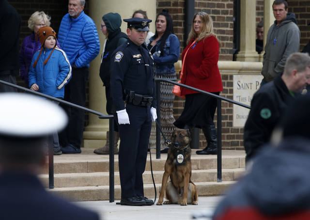 A Hilliard, Ohio, K-9 unit stands outside St. Paul the Apostle Catholic Church in Westerville, Ohio, before funeral services for Westerville police officers Anthony Morelli and Eric Joering Friday, Feb. 16, 2018. The two veteran officers were shot after entering a residence Saturday. The officers returned fire, wounding 30-year-old Quentin Smith, who has been charged with aggravated murder and remains hospitalized. (AP Photo/Paul Vernon)