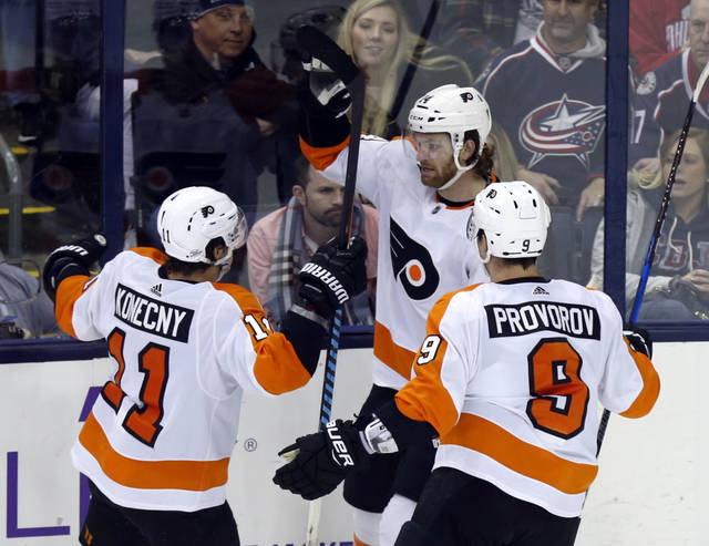 Philadelphia Flyers forward Travis Konecny, left, forward Sean Couturier, center, and defenseman Ivan Provorov, of Russia, celebrate Couturier's overtime goal against the Columbus Blue Jackets during an NHL hockey game in Columbus, Ohio, Friday, Feb. 16, 2018. The Flyers won 2-1. (AP Photo/Paul Vernon)