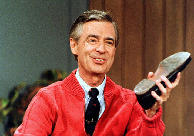 """FILE - This June 28, 1989, file photo, shows Fred Rogers as he rehearses the opening of his PBS show """"Mister Rogers' Neighborhood"""" during a taping in Pittsburgh. It's been 50 years since Fred Rogers first appeared on our TVs, a gentle and avuncular man who warbled """"Won't You Be My Neighbor?"""" The golden anniversary of America's favorite neighbor's appearance is being celebrated with a PBS special next month, a new stamp, a feature-length documentary coming out this summer and plans for a Tom Hanks-led biopic. (AP Photo/Gene J. Puskar, File)"""