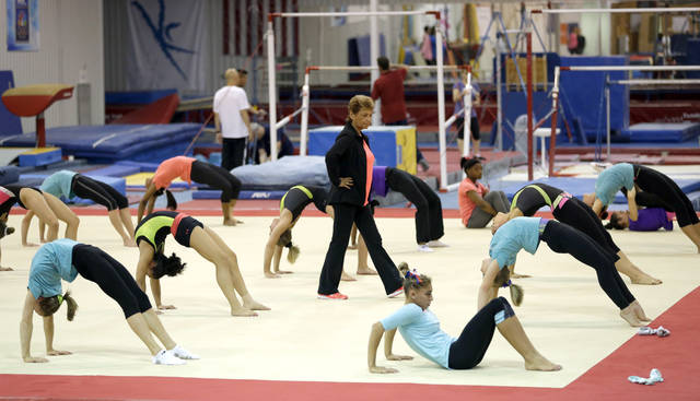 In this Sept. 12, 2015, file photo, Martha Karolyi, national team coordinator for USA Gymnastics, watches over gymnasts during a training session at the Karolyi Ranch in Huntsville, Texas. Much of the widespread culture of abuse in USA Gymnastics, AP found, can be traced to the training methods of the Karolyis. The Romanian-born couple gradually assumed leadership of the U.S. women's gymnastics program after defecting to the United States in 1981. They trained hundreds of gymnasts at their complex in rural Huntsville, Texas, selected gymnasts for the national team, and earned millions from USA Gymnastics. (AP Photo/David J. Phillip, File)