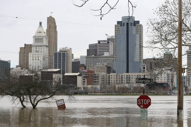 View looking north to Cincinnati as flood waters rise toward the intersection of Riverside Drive and Garrard Street, Sunday, Feb. 25, 2018, in Covington, Ky. The Ohio River is expected to crest at 60.7 feet by Sunday evening, according to the National Weather Service. The river rose above the 60 feet mark for the first time in two decades Sunday morning. (Kareem Elgazzar/The Cincinnati Enquirer via AP)
