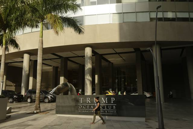 A woman past walks past the main entrance to the Trump Ocean Club International Hotel and Tower in Panama City, Friday, Feb. 23, 2018. One of President Donald Trump's family businesses is battling an effort to physically evict its team of executives from a luxury hotel in Panama where they manage operations, and police have been called to keep the peace, The Associated Press has learned. Witnesses told the AP they saw Trump's executives carrying files to a room for shredding. (AP Photo/Arnulfo Franco)