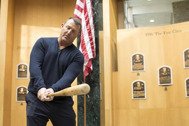 In this photo provided by the National Baseball Hall of Fame and Museum, former Cleveland Indians slugger Jim Thome demonstrates his swing in the Plaque Gallery during his orientation tour of the National Baseball Hall of Fame and Museum, Tuesday, Feb. 27, 2018, in Cooperstown, N.Y., to prepare for his induction this summer. (Milo Stewart Jr./National Baseball Hall of Fame and Museum via AP)