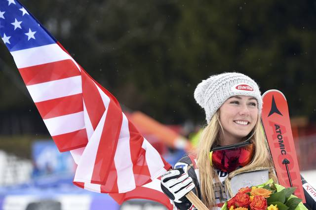 United States' Mikaela Shiffrin holds a US flag as she celebrates after winning an alpine ski, women's World Cup slalom, in Ofterschwang, Germany, Saturday, March 10, 2018. (AP Photo/Marco Tacca)
