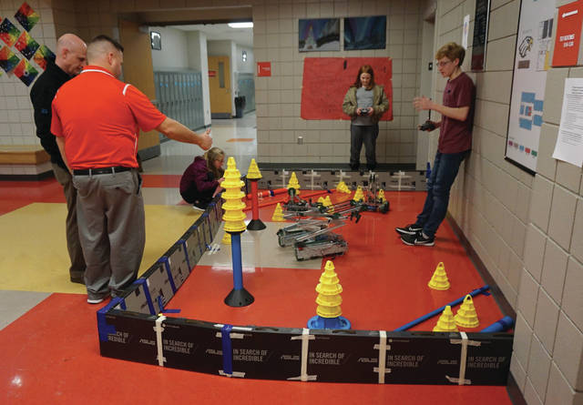 STEAM teacher Doug Eckelbarger (red shirt) explains a robotics display to a parent as 8th-grader Ryan Grudell (against wall) controls a robot during a Big Walnut Middle School Student Showcase in February.