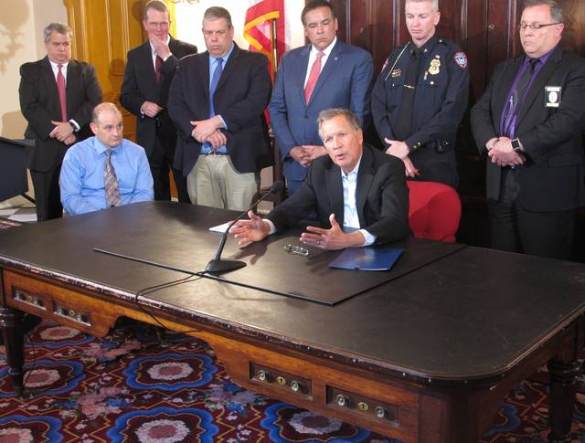 Ohio Gov. John Kasich discusses the need to improve the speed and accuracy of the reporting of information about individuals prohibited under law from having a gun to a national background check database, Monday, April 23, 2018, in Columbus, Ohio. Kasich, a Republican, signed an executive order commissioning reports about the problem, at an event with police chiefs, the mayor of Columbus and police union officials. (AP Photo/Andrew Welsh-Huggins)
