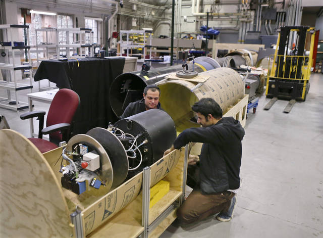 In this photo made on Wednesday, April 4, 2018, David Kohandash, left, and Mohammad Mousaei work on the RadPiper robot in the robotics institute at Carnegie-Mellon University in Pittsburgh. The mechanism is designed to measure potentially hazardous radiation is intended to go through pipes at a former uranium plant being cleaned up in southern Ohio. (AP Photo/Keith Srakocic)