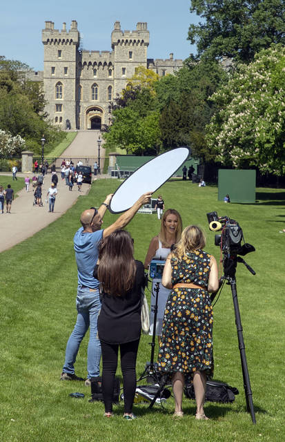 British TV presenter Amanda Holden, centre of group, reacts during filming for the US television show Inside Edition, on the Long Walk in Windsor, England, Monday May 14, 2018, ahead of the May 19 wedding of Britain's Prince Harry and Meghan Markle. Worldwide media outlets begin setting up for their coverage of the marriage upcoming weekend, reporting from the town of Windsor. (Steve Parsons/PA via AP)