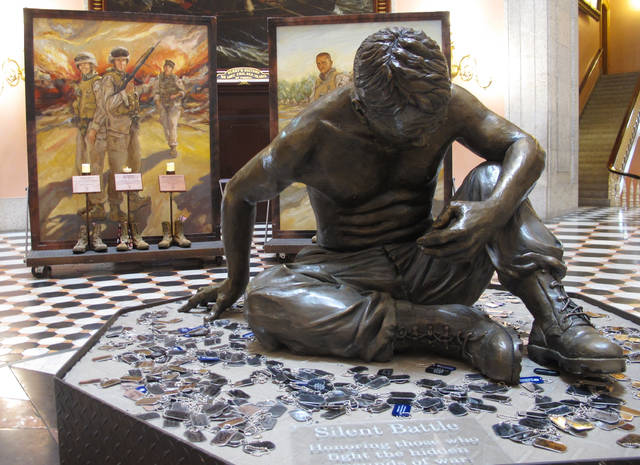 """This Monday, May 21, 2018, photo shows a memorial paying tribute to a central Ohio-based Marine reserve company that lost 22 Marines and a Navy Corpsman in Iraq in 2005, including a newly unveiled bronze statute, """"Silent Battle,"""" drawing attention to suicides among veterans, is displayed at the Ohio Statehouse in Columbus, Ohio. (AP Photo/Andrew Welsh-Huggins)"""