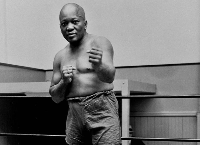 FILE - In this 1932 file photo, boxer Jack Johnson, the first black world heavyweight champion, poses in New York City. President Donald Trump on Thursday, May 24, 2018, granted a rare posthumous pardon to boxing's first black heavyweight champion, clearing Jack Johnson's name more than 100 years after a racially-charged conviction.   (AP Photo/File)
