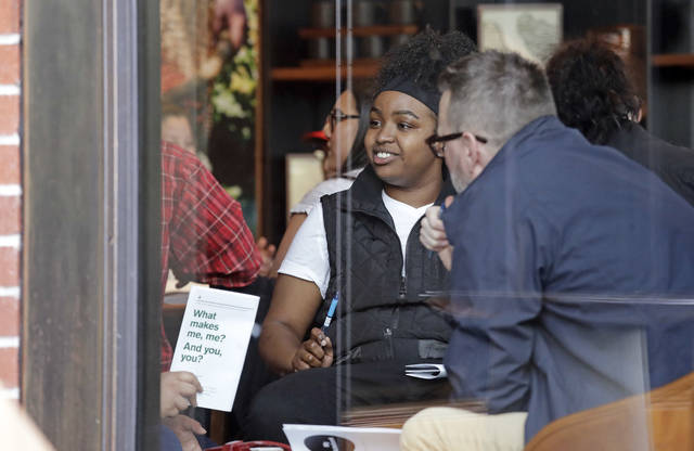 People are seen meeting inside the ground floor, closed Starbucks Reserve at the company's headquarters during employee anti-bias training, Tuesday, May 29, 2018, in Seattle. Starbucks closed more than 8,000 stores nationwide on Tuesday to conduct anti-bias training, the next of many steps the company is taking to try to restore its tarnished image as a hangout where all are welcome. (AP Photo/Elaine Thompson)