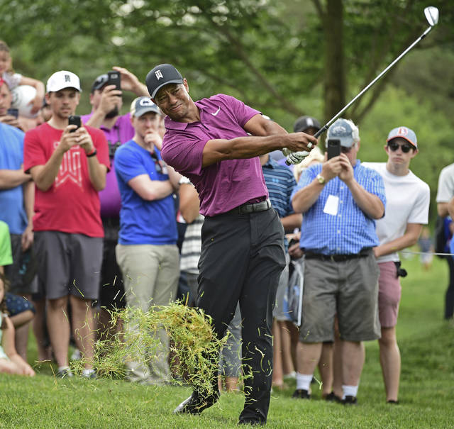 Tiger Woods follows through on his swing from the rough on the eleventh hole during the pro-am for the the Memorial golf tournament Wednesday, May 30, 2018, in Dublin, Ohio. (AP Photo/David Dermer)