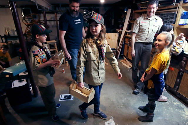 "FILE - In this March 1, 2018, file photo, Tatum Weir, center, carries a tool box she built as her twin brother Ian, left, follows after a Cub Scout meeting in Madbury, N.H. Fifteen communities in New Hampshire are part of an ""early adopter"" program to allow girls to become Cub Scouts and eventually Boy Scouts. For 108 years, the Boy Scouts of America's flagship program for older boys has been known simply as the Boy Scouts. With girls soon entering the ranks, the BSA says that iconic name will change to ""Scouts BSA."" The change will take effect in February 2019. (AP Photo/Charles Krupa, File)"