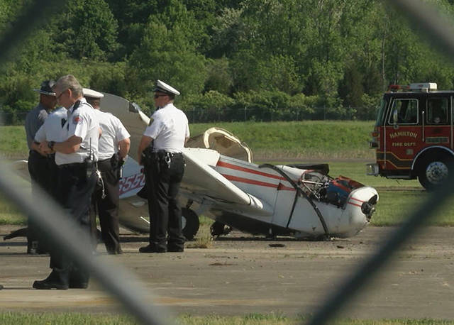 In this frame from video, police investigate a plane crash at the Butler County Regional Airport on Tuesday, May 15, 2018, in Hamilton, Ohio. The pilot of a single-engine plane that crashed during takeoff has been flown by helicopter to a Cincinnati hospital to be treated for injuries. (Mike Woeste/WXIX FOX19 Now via AP)