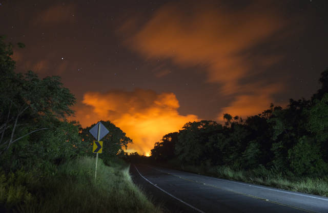 Volcanic activity from the Malama Ki and Leilani Estates neighborhoods glows in the distance from Hwy 137, Thursday, May 17, 2018, near Pahoa, Hawaii. (AP Photo/Marco Garcia)
