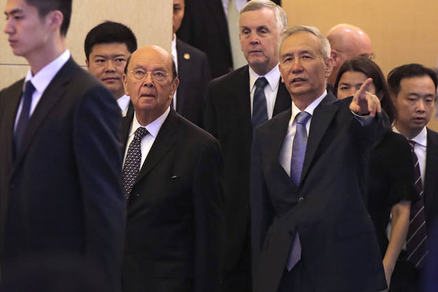 U.S. Commerce Secretary Wilbur Ross, second from left, and Chinese Vice Premier Liu He, right, arrive to attend a meeting at the Diaoyutai State Guesthouse in Beijing, Sunday, June 3, 2018. U.S. Commerce Secretary Ross is in Beijing for talks on China's promise to buy more American goods after Washington ratcheted up tensions with a new threat of tariff hikes on Chinese high-tech exports. (AP Photo/Andy Wong, Pool)