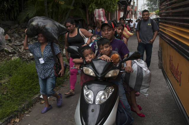 Residents evacuate after a new flow of searing hot volcanic material moved down the slopes of the Volcano of Fire in Escuintla, Guatemala, Tuesday, June 5, 2018. The volcano exploded Sunday, sending down hot clouds of gas and ash that killed at least 70 people in communities on its flanks. Rescuers were also evacuated Tuesday. (AP Photo/Oliver de Ros)