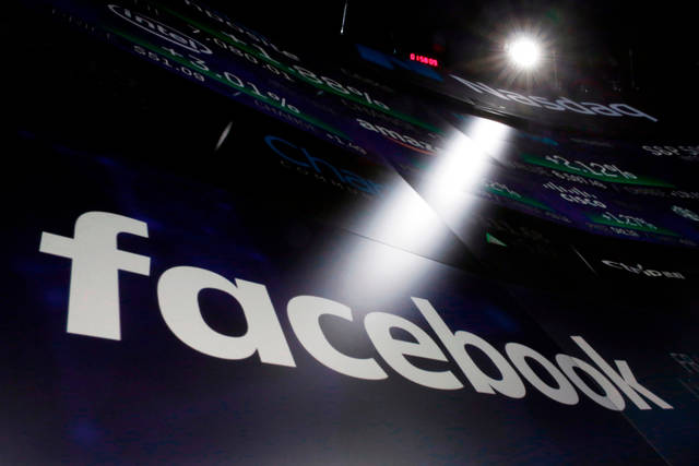 FILE- In this March 29, 2018, file photo the logo for Facebook appears on screens at the Nasdaq MarketSite in New York's Times Square. Facebook says a software bug made some private posts public for as many as 14 million users for several days in May. (AP Photo/Richard Drew, File)