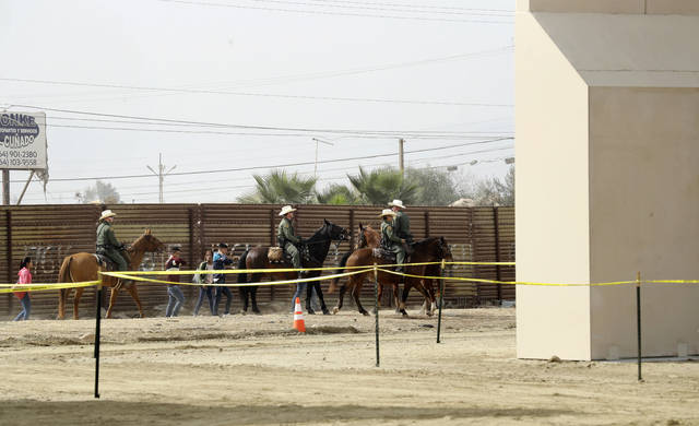 FILE - In this Oct. 19, 2017, file photo, a group of people are detained by Border Patrol agents on horseback after crossing the border illegally from Tijuana, Mexico, near where prototypes for a border wall, right, were being constructed in San Diego. More than 1,600 people arrested at the U.S.-Mexico border, including parents who have been separated from their children, are being transferred to federal prisons, U.S. immigration authorities confirmed Thursday, June 7, 2018. They said they're running out of room at their own facilities amid President Donald Trump's crackdown on illegal immigration. The move drew condemnation from activists who said the detainees may have legitimate claims to asylum and don't deserve to be held in federal prisons. (AP Photo/Gregory Bull, File)