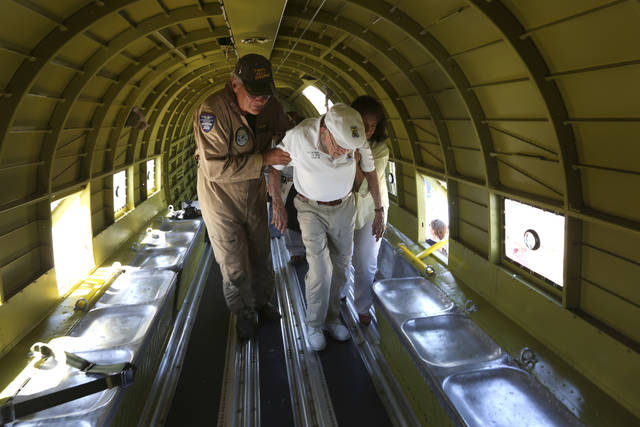 "In this Wednesday, June 6, 2018 photo, Richard ""Dick"" Cole, the last surviving member of the famed World War II Doolittle Tokyo Raiders, is help to a seat in a C-47 cargo plane at the Commemorative Air Force's San Marcos, Texas, facility as part of the organization's D-Day ceremonies. The recently-restored and now San Marcos-based C-47, nicknamed That's All Brother, was the lead aircraft across the English Channel on D-Day. The CAF is making plans to fly the aircraft to England in 2019 to take part in the 75th anniversary of the event. (William Luther/The San Antonio Express-News via AP)"