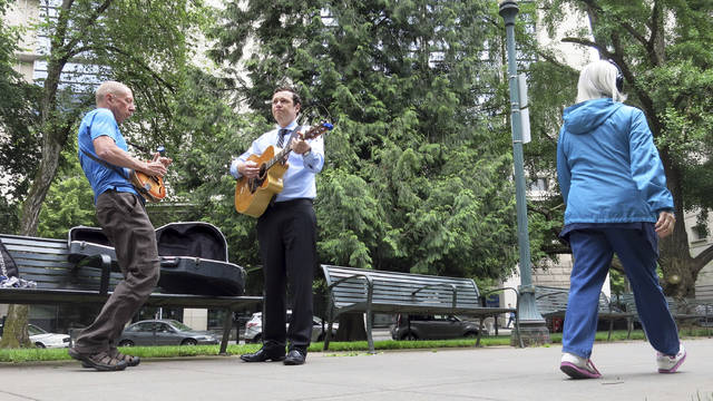 Mack Stilson, left, plays his mandolin and Victor Reuther, right, plays his guitar in a park in Portland, Ore., as they practice for an upcoming bluegrass gig during their lunch hour on June 7, 2018. Stilson and Reuther, both Portland residents, say they are proud of the city's reputation for activism but they are concerned about dueling demonstrations that have turned violent in the past year in downtown Portland. A right-wing group called Patriot Prayer and self-described left-wing anti-fascists clashed in the streets on June 3, in some cases drawing blood, and police made four arrests. (AP Photo/Gillian Flaccus)