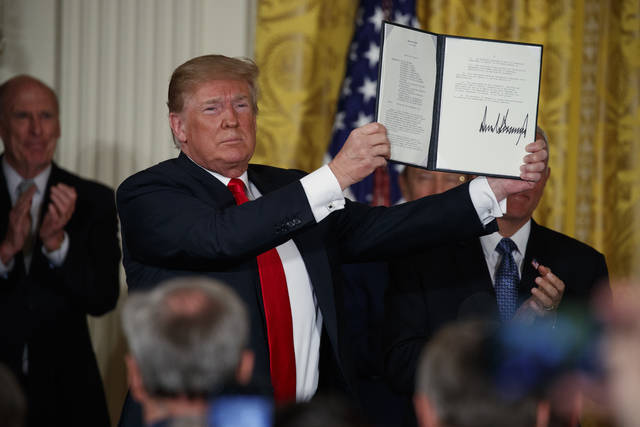 "President Donald Trump shows off a ""Space Policy Directive"" after signing it during a meeting of the National Space Council in the East Room of the White House, Monday, June 18, 2018, in Washington. (AP Photo/Evan Vucci)"