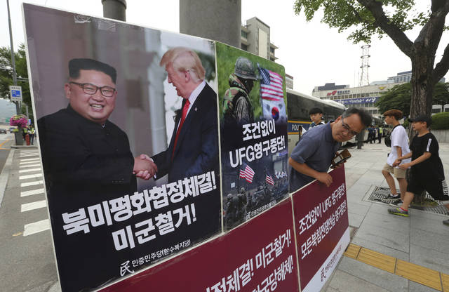 """A photo showing U.S. President Donald Trump and North Korean leader Kim Jong Un is displayed as a member of People's Democratic Party stands to oppose military exercises between the United States and South Korea near the U.S. embassy in Seoul, South Korea, Tuesday, June 19, 2018. The Pentagon on Monday, June 18, 2018, formally suspended a major military exercise planned for August with South Korea, a much-anticipated move stemming from Trump's nuclear summit with Kim. The signs read: """" Stop Ulchi Freedom Guardian (UFG) exercises and withdrawal of U.S. troops."""" (AP Photo/Ahn Young-joon)"""