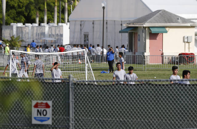 Immigrant children play outside a former Job Corps site that now houses them, Monday, June 18, 2018, in Homestead, Fla. It is not known if the children crossed the border as unaccompanied minors or were separated from family members. Wrenching scenes of migrant children being separated from their parents at the southern border are roiling campaigns ahead of midterm elections, emboldening Democrats on the often-fraught issue of immigration  (AP Photo/Wilfredo Lee)