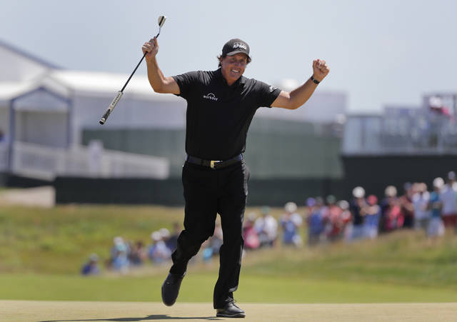FILE - In this June 17, 2018, file photo, Phil Mickelson reacts after sinking a putt on the 13th hole during the final round of the U.S. Open Golf Championship, in Southampton, N.Y. Mickelson brought attention to a tough setup on Saturday when he intentionally hit a putt with the ball still rolling and was penalized. (AP Photo/Frank Franklin II, File)
