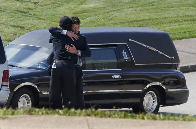 A person attending the funeral for Antwon Rose Jr. embraces a police officer near the hearse on Monday, June 25, 2018, in Swissvale, Pa. Rose was fatally shot by a police officer seconds after he fled a traffic stop June 19, in the suburb of East Pittsburgh. (AP Photo/Keith Srakocic)