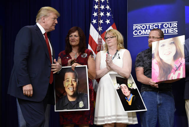 President Donald Trump, left, arrives for an event on the White House complex in Washington, Friday, June 22, 2018, with people who have lost family members from crime committed by undocumented immigrants. (AP Photo/Susan Walsh)