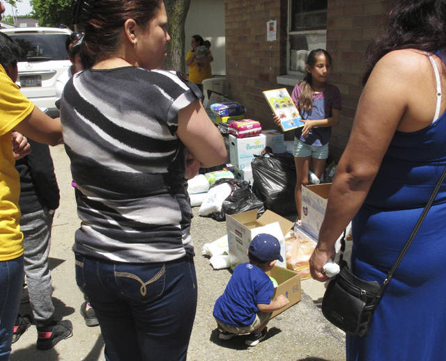 In this Friday, June 15, 2018 photo, a boy picks out a soccer ball from donations delivered to an Ohio trailer park in Norwalk, Ohio. Community members have donated diapers, baby wipes, food and clothing for the families of workers arrested in an immigration raid at a garden and landscaping company in early June. (AP Photo/John Seewer)