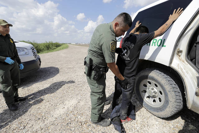 U.S. Border Patrol agent Rene Cisneros gives migrant Gerberht Caraac, from Guatemala, a pat-down after he was caught trying to illegally enter the United States, Monday, June 25, 2018, in Hidalgo, Texas. (AP Photo/David J. Phillip)