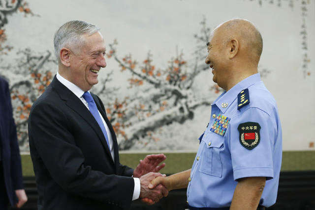 U.S. Defense Secretary Jim Mattis, left, is welcomed by China's Vice Chairman of the Central Military Commission Xu Qiliang at the Bayi Building in Beijing Thursday, June 28, 2018. (Thomas Peter/Pool Photo via AP)