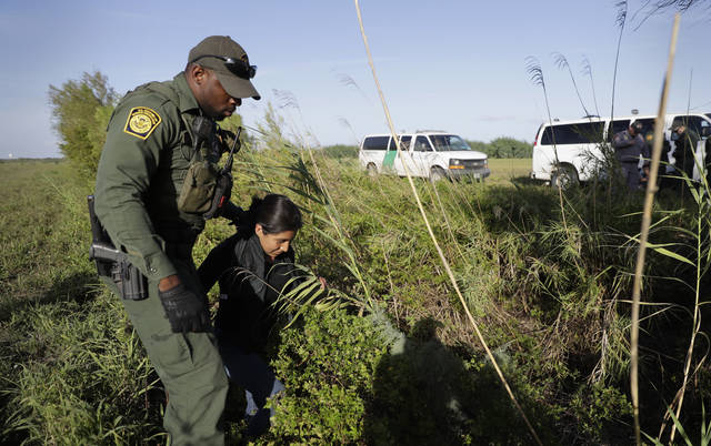 "FILE - In this Aug. 11, 2017 file photo a U.S. Customs and Border Patrol agent escorts an immigrant suspected of crossing into the United States illegally along the Rio Grande near Granjeno, Texas. A U.S. official tells The Associated Press that Border Patrol arrests fell sharply in June 2018 to the lowest level since February, ending a streak of four straight monthly increases. The drop may reflect seasonal trends or it could signal that President Donald Trump's ""zero-tolerance"" policy to criminally prosecute every adult who enters the country illegally is having a deterrent effect. The official spoke on condition of anonymity because the numbers are not yet intended for public release. (AP Photo/Eric Gay, File)"
