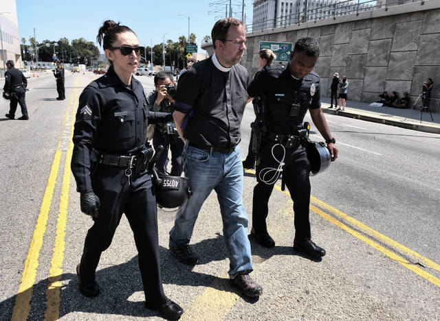 A member of the clergy is taken away in handcuffs after being arrested protesting in front of the Immigration and Customs Enforcement facility in downtown Los Angeles on Monday, July 2, 2018. A group of 17 protesters sat down in the street, blocking the entrance to the ICE facility Monday morning. (AP Photo/Richard Vogel)