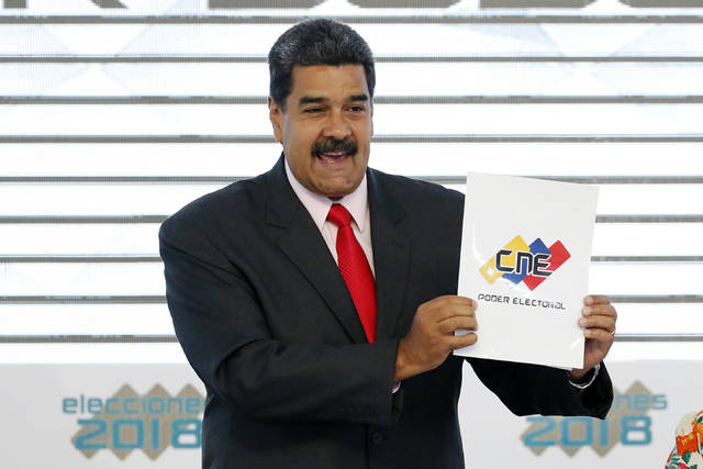 FILE - In this May 22, 2018, file photo, Venezuela's President Nicolas Maduro holds up the National Electoral Council certificate declaring him the winner of the presidential election, during a ceremony at CNE headquarters in Caracas, Venezuela. As a meeting last August in the Oval Office to discuss sanctions on Venezuela was concluding, President Donald Trump turned to his top aides and asked an unsettling question: With a fast unraveling Venezuela threatening regional security, why can't the U.S. just simply invade the troubled country? (AP Photo/Ariana Cubillos, File)