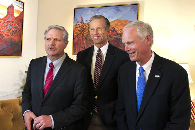 U.S. Sen. John Hoeven, R-N.D., left, Sen. John Thune, R-S.D., center, and Sen. Jerry Moran, R-Kan., chairman of the Subcommittee on Consumer Protection, Product Safety, Insurance, and Data Security, speak to the Associated Press in the U.S. Embassy in Moscow, Russia, Wednesday, July 4, 2018. A U.S. senator who is part of a congressional delegation visiting Russia says Moscow could help improve ties by not meddling in the midterm U.S. election in November. (AP Photo/Maria Danilova)