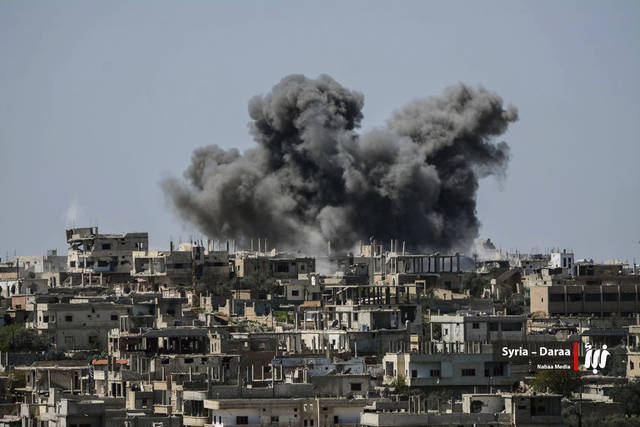 This Thursday, July 5, 2018 photo provided by Nabaa Media, a Syrian opposition media outlet, shows smoke rising over buildings that were hit by Syrian government forces bombardment, in Daraa province, southern Syria. Syrian state media and a war monitor say government forces have captured new areas along the border with Jordan and are on the verge of reaching a main crossing between the two countries. (Nabaa Media, via AP)