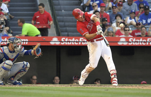 Los Angeles Angels' Mike Trout, right, hits a solo home run as Los Angeles Dodgers catcher Yasmani Grandal watches during the sixth inning of a baseball game Saturday, July 7, 2018, in Anaheim, Calif. (AP Photo/Mark J. Terrill)