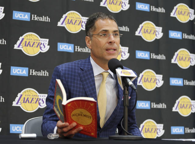 """Los Angeles Lakers general manager Rob Pelinka reads a passage from """"The Alchemist"""" by Paulo Coelho as talks about the acquisition of LeBron James and other free agents at a news conference at the NBA basketball team's headquarters in El Segundo, Calif., Wednesday, July 11, 2018. (AP Photo/Reed Saxon)"""