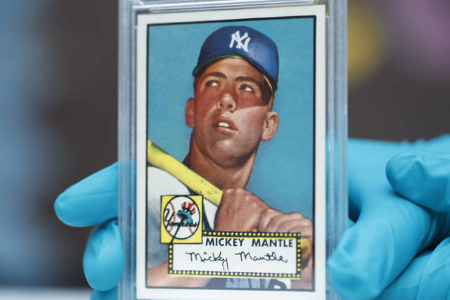 """The """"Holy Grail"""" of baseball cards, a 1952 Topps Mickey Mantle that is valued at more than $10 million, is put on display as part of baseball memorabilia exhibit at the Colorado History Museum Monday, July 16, 2018, in Denver. The pristine card, one of three known to still be in existence, is owned by Denver lawyer Marshall Fogell. (AP Photo/David Zalubowski)"""