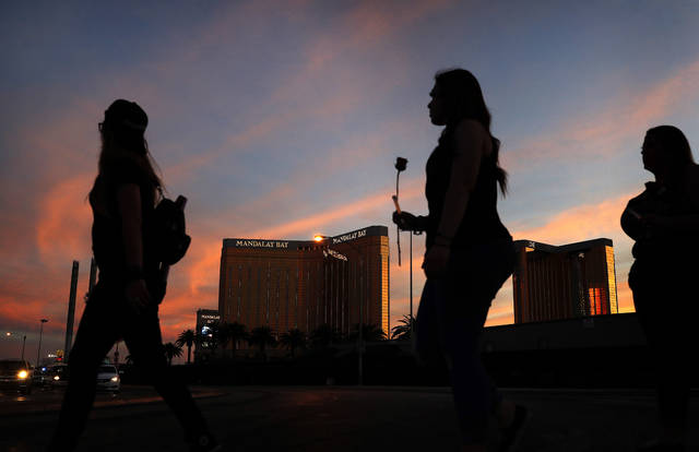 "FILE - In this April 1, 2018 file photo, people carry flowers as they walk near the Mandalay Bay hotel and casino during a vigil for victims and survivors of a mass shooting in Las Vegas. MGM Resorts International has sued hundreds of victims of the deadliest mass shooting in modern U.S. history in a bid to avoid liability for the gunfire that rained down from its Mandalay Bay casino-resort in Las Vegas. The company argues in lawsuits filed Friday, July 13, 2018, in Nevada and California that it has ""no liability of any kind"" to survivors or families of slain victims under a federal law enacted after the Sept. 11 terrorist attacks. (AP Photo/John Locher, File)"
