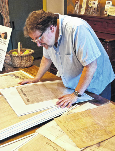 Benny Shoults, curator of the Meeker Homestead Museum, looks through the many different newspapers that at one time or another was a part of the Delaware County community. The newspaper that he is closely inspecting is the Loco Foco.