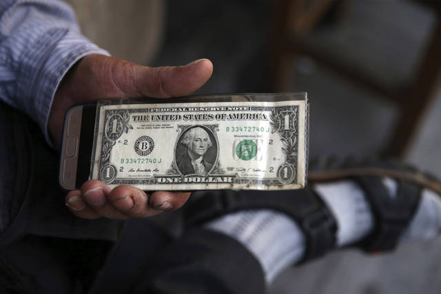 An Iranian street money exchanger holds a U.S. banknote in downtown Tehran, Iran, Monday, July 30, 2018. Iran's currency has dropped to a record low ahead of the imposition of renewed American sanctions, with many fearing prolonged economic suffering or possible civil unrest. (AP Photo/Vahid Salemi)
