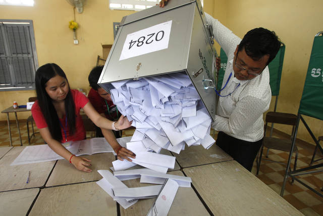 Polling station officials empty ballots boxes before counting at a polling station in Phnom Penh, Cambodia, Sunday, July 29, 2018. With the main opposition silenced, Cambodians were voting in an election Sunday virtually certain to return to office Prime Minister Hun Sen and his party who have been in power for more than three decades. (AP Photo/Heng Sinith)
