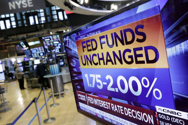 A screen on the floor of the New York Stock Exchange shows the rate decision of the Federal Reserve, Wednesday, Aug. 1, 2018. The Federal Reserve is leaving its benchmark interest rate unchanged while signaling further gradual rate hikes in the months ahead as long as the economy stays healthy. (AP Photo/Richard Drew)