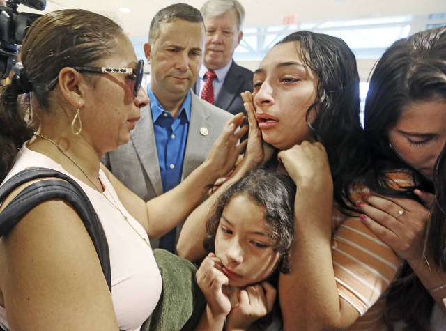 CORRECTS AGE TO 39-Alejandra Juarez,39, left, says goodbye to her children, Pamela and  Estela at the Orlando International Airport on Friday, Aug. 3, 2018 in Orlando, Fla.  Juarez, the wife of a former Marine is preparing to self-deport to Mexico in a move that would split up their family.  (Red Huber/Orlando Sentinel via AP)