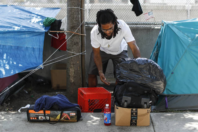 "Residents and supporters of a homeless encampment along Third St. remove their belongings before Cincinnati officials arrive to clean the area., Friday, Aug. 3, 2018, in Cincinnati. A federal judge refused to block the city cleanup after the advocates sued to stop it. They called an order to vacate ""a bullying tactic"" that violates constitutional rights of the homeless. (AP Photo/John Minchillo)"