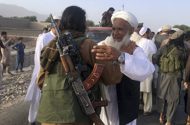 FILE - In this June 16, 2018, file photo, Taliban fighters gather with residents to celebrate a three-day cease fire marking the Islamic holiday of Eid al-Fitr, in Nangarhar province, east of Kabul, Afghanistan. In a rare diplomatic foray and the strongest sign yet of the Taliban's increasing political presence in the region, the head of the militant group's political office led a delegation to Uzbekistan to meet senior Foreign Ministry officials, Uzbek and Taliban officials said Saturday, Aug. 11, 2018. (AP Photo/Rahmat Gal, File)